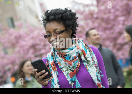 A group of people under the cherry blossom trees in the park A young woman smiling and checking her phone - Stock Photo