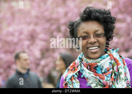 A group of people cherry blossom trees in the park A young woman smiling and looking at the camera Wearing a floral - Stock Photo