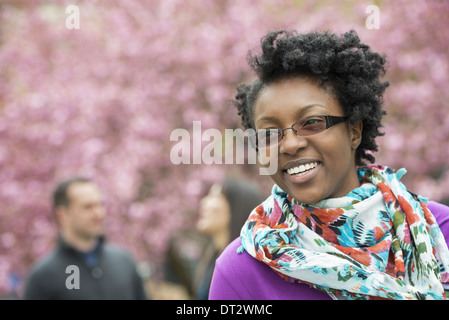 A group of people under the cherry blossom trees in the park A young woman smiling wearing a purple shirt and floral - Stock Photo