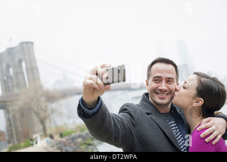 Brooklyn Bridge crossing over the East River A couple taking a picture with a phone a selfy of themselves - Stock Photo