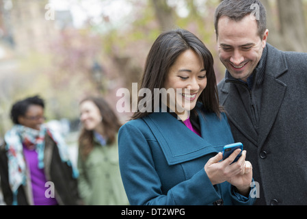 A group of people in a city park A man in a grey coat and a woman in a turquoise coat both looking at a smart phone - Stock Photo