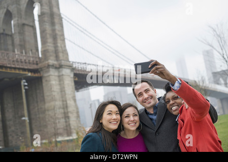 New York city The Brooklyn Bridge crossing over the East River Four friends taking a picture with a phone a selfy - Stock Photo