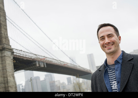 New York city the Brooklyn Bridge crossing over the East River A man wearing a grey coat smiling at the camera - Stock Photo