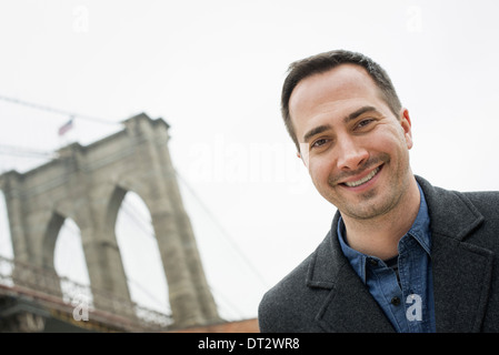 New York city the Brooklyn Bridge crossing over the East River A man looking at the camera and smiling - Stock Photo