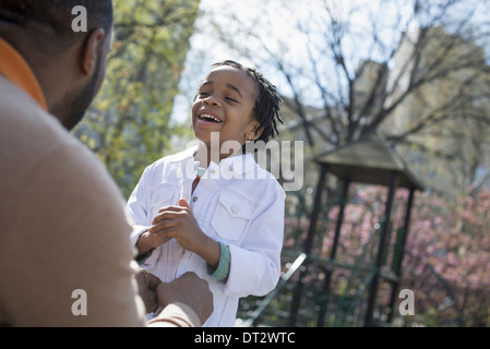 A father kneeling and buttoning his son's jacket - Stock Photo