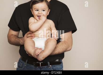 A young boy wearing cloth diapers being held by his father in his arms - Stock Photo
