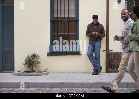 Outdoors in the city in spring A couple walking on the sidewalk and a man leaning against a wall checking his phone - Stock Photo