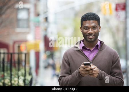 A young man holding his phone and smiling at the camera