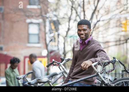 A young man smiling at the camera Bicycle rack - Stock Photo