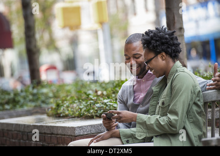 A couple sitting side by side and looking at a phone screen - Stock Photo