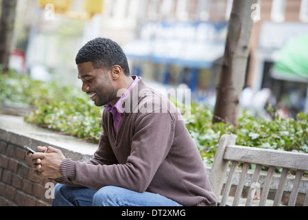 A young man sitting on a bench checking his phone and texting - Stock Photo