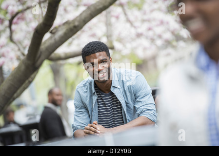 A man sitting at a table smiling A woman in the foreground - Stock Photo