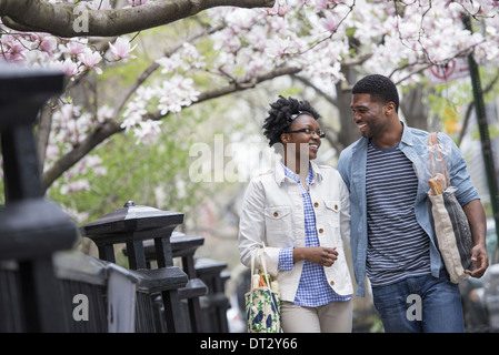 A couple walking in the park side by side carrying shopping bags - Stock Photo