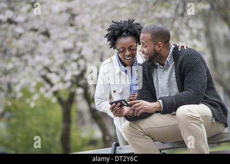 A couple sitting on a bench one holding a phone - Stock Photo