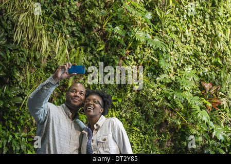 A couple standing in front of a wall covered with lush thick foliage - Stock Photo