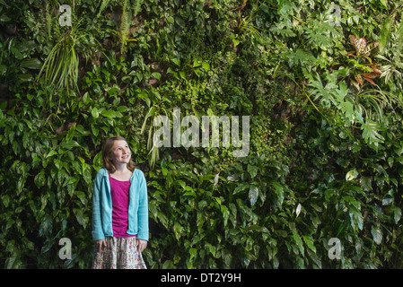 city in spring An urban lifestyle A young girl standing in front of a wall covered with ferns and climbing plants - Stock Photo