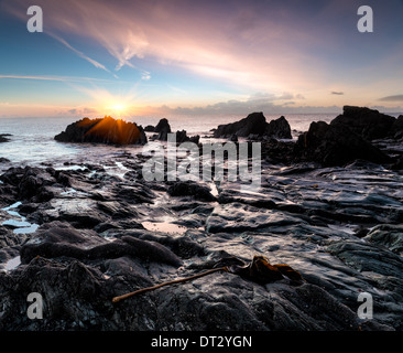 Ocean sunrise on a rocky beach at Looe in south Cornwall - Stock Photo