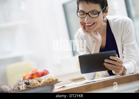 New York City A woman dressed for work in cream jacket holding a cup of coffee Checking her digital tablet - Stock Photo