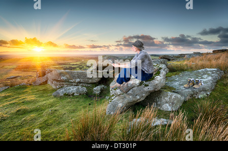 Woman out hiking, relaxing and using a tablet pc at sunset on a rocky tor on Bodmin Moor in Cornwall - Stock Photo