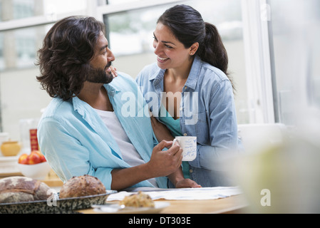 An office or apartment interior in New York City A couple side by side by the breakfast bar Food and fresh fruit - Stock Photo
