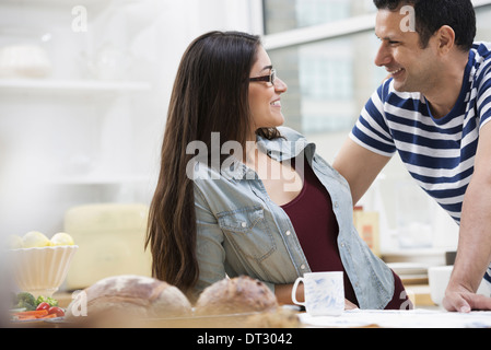 An office or apartment interior in New York City Two people a couple beside the breakfast bar - Stock Photo