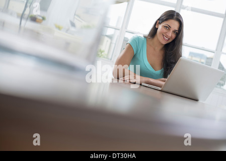A young woman sitting comfortably in a quiet airy office environment Using a laptop