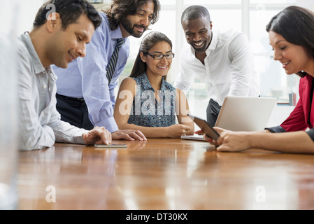Business people gathered in an office in the city A team of five people men and women gathering around a laptop - Stock Photo
