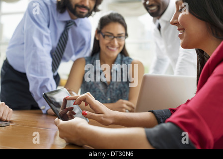 Business people gathered in an office in the city A team of four people men and women gathering around a laptop - Stock Photo