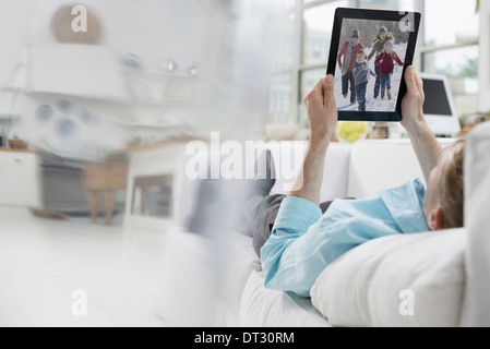 A man lying on a sofa in comfort in a quiet airy office environment Using a digital tablet - Stock Photo