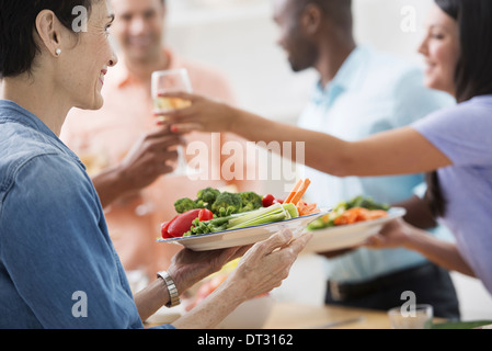 A working lunch a salad buffet A woman holding out a glass of wine and a plate of food - Stock Photo
