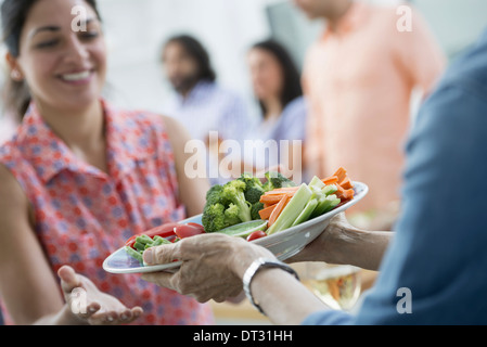 salad buffet of mixed ages and ethnicities meeting together - Stock Photo