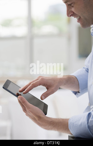 Professionals in the office A light and airy place of work A man in a white shirt using a digital tablet - Stock Photo