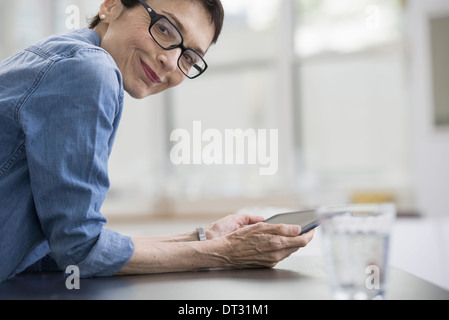 Professionals in the office A light and airy place of work A mature woman in a blue denim shirt holding a digital - Stock Photo