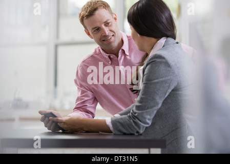 Professionals in the office A light and airy place of work Two people sitting at a desk using a digital tablet Work - Stock Photo