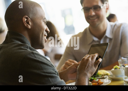 Two men seated at a cafe table having a meal - Stock Photo