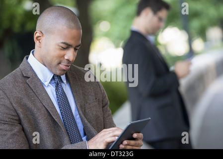 Man using a digital tablet and one checking a smart phone - Stock Photo
