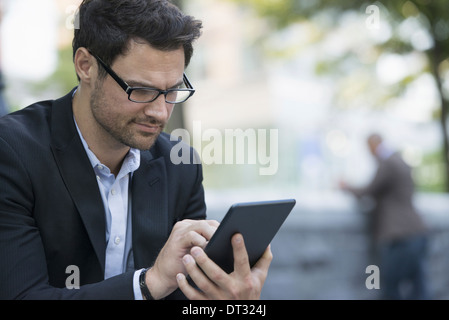 Two men in the park one using a digital tablet and one checking a smart phone - Stock Photo