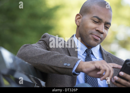 A man seated on a bench Checking his cell phone - Stock Photo