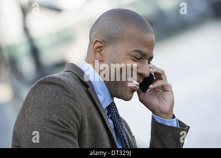 A man seated on a bench making a call on his smart phone - Stock Photo