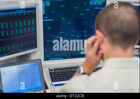 An air traffic controller in the air traffic control centre of 'Skyguide' is navigating aircrafts through Switzerland's - Stock Photo