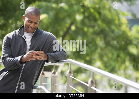 A man in a sweatshirt looking at his smart phone - Stock Photo