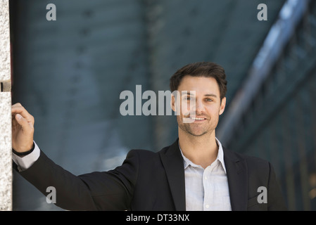 A man in a black jacket and open collared shirt - Stock Photo