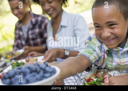 A family picnic in a shady woodland Adults and children sitting at a table - Stock Photo