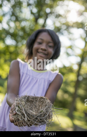 A child a young girl smiling and holding out a bird's nest in her hands - Stock Photo