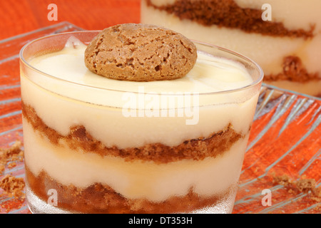 Close-up of vanilla custard and amaretti dessert served in glass cups over an orange background. Selective focus. - Stock Photo