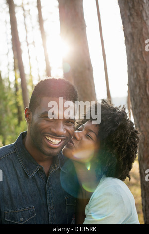 A couple a young woman kissing a man on the cheek - Stock Photo