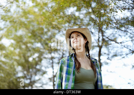 A girl in a straw hat walking in the woods - Stock Photo