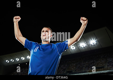 Soccer player cheering in stadium - Stock Photo