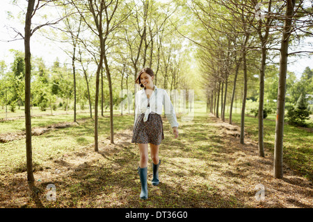 A young woman walking down an avenue of trees in woodland - Stock Photo
