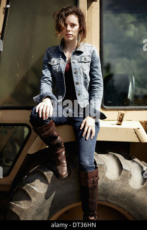 A young woman in denim jacket and boots on the hood of a tractor - Stock Photo